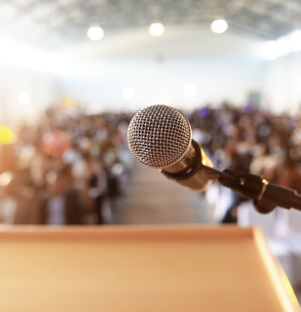 Microphone in front of podium with crowd in the background